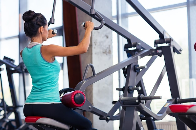 Vue arrière portrait d'une séance d'entraînement de femme sportive sur la machine d'exercices dans la salle de fitness