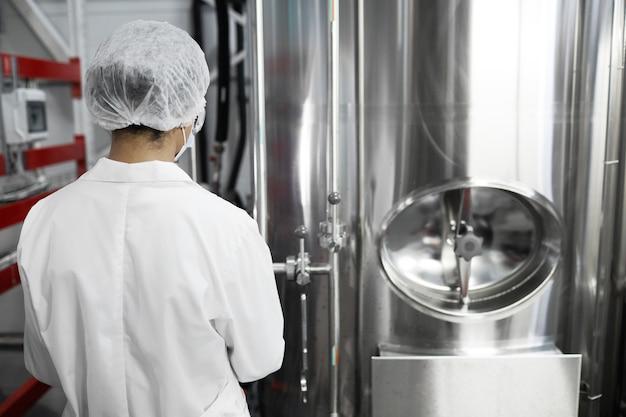 Vue arrière portrait d'une travailleuse portant des vêtements de protection lors de l'utilisation d'équipements dans une usine chimique, espace pour copie