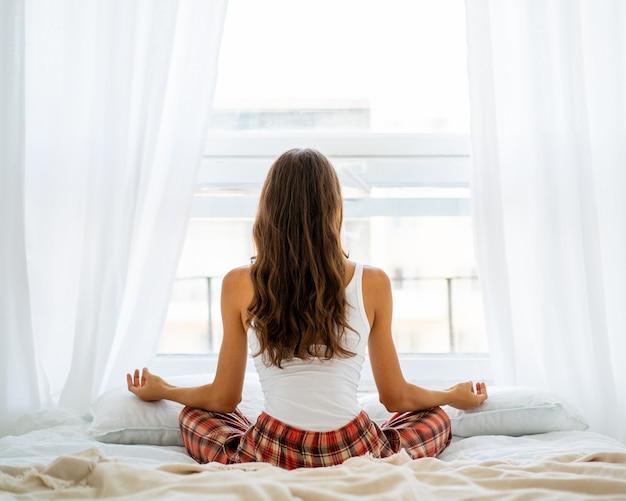 Vue arrière de la pose de yoga femme au lit après le réveil, entrant dans le nouveau jour