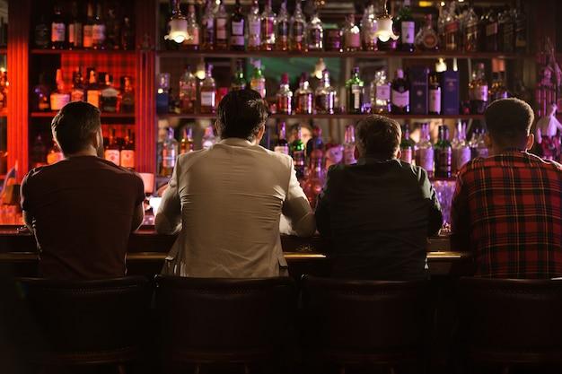 Vue arrière de quatre jeunes hommes buvant de la bière