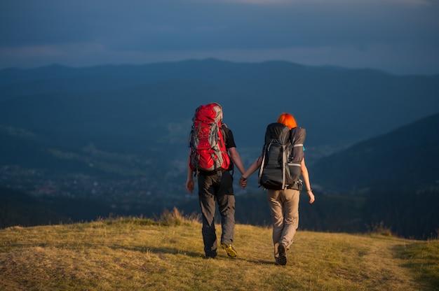 Vue arrière de randonneurs de couple avec sacs à dos à pied le long d'une route