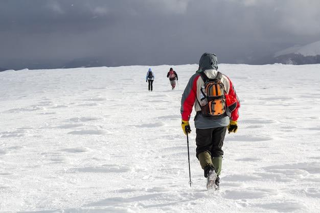 Vue arrière des randonneurs marchant sur la colline couverte de neige dans les montagnes d'hiver.