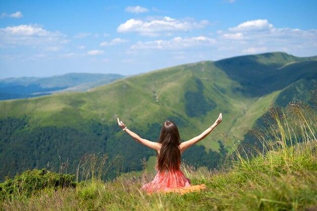 Vue arrière d'une randonneuse heureuse en robe rouge assise sur une colline herbeuse par une journée venteuse dans les montagnes d'été avec les bras tendus, profitant de la vue sur la nature.