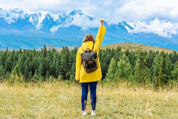 Vue arrière d'une randonneuse avec un sac à dos se penche sur les montagnes dans la pose d'un gagnant lors d'un voyage de vacances. concept de voyage et d'aventure