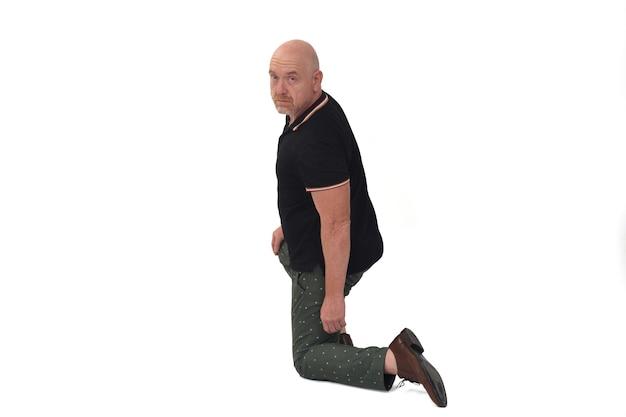 Vue arrière et regardant la caméra de l'homme appuyé sur un genou au sol sur fond blanc