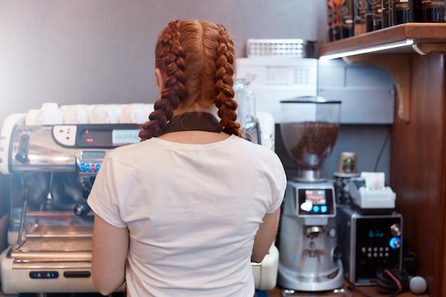 Vue arrière de la serveuse faisant la commande de son client au café. serveuse posant à l'envers