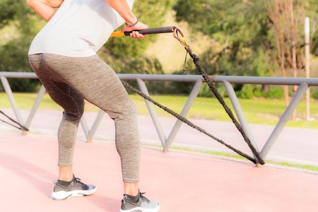 Vue arrière d'un sportif athlétique faisant de l'exercice avec un bâton de gymnastique élastique dans le parc. homme adulte exerçant à l'extérieur.
