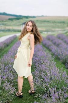 Vue arrière d'une superbe jeune fille en robe jaune clair profitant d'une promenade dans un champ de lavande en été