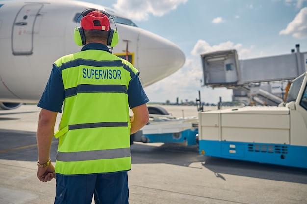 Vue arrière d'un superviseur dans un gilet réfléchissant debout devant le véhicule aérien
