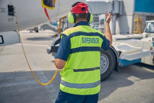 Vue arrière d'un superviseur de maintenance d'aéronefs caucasien qualifié dans un casque dirigeant un opérateur de tracteur de refoulement