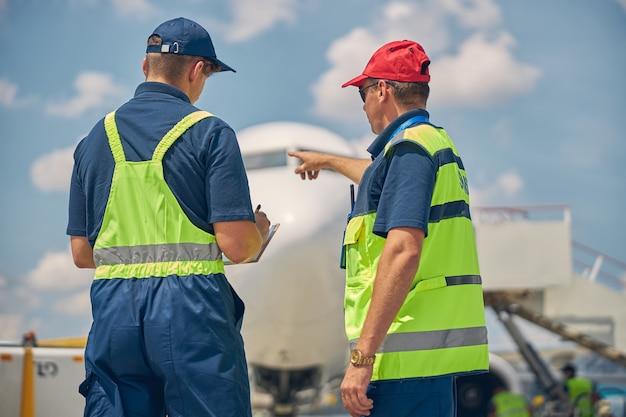 Vue arrière d'un technicien d'entretien d'aéronefs pointant vers l'avion garé à son collègue