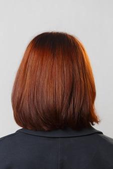 Vue arrière de la tête de femme aux cheveux bruns teints.