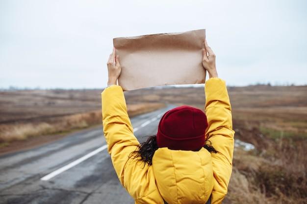Vue arrière d'une touriste portant une veste jaune et un chapeau rouge se dresse avec une affiche en papier vierge sur le côté d'une route d'hiver vide.