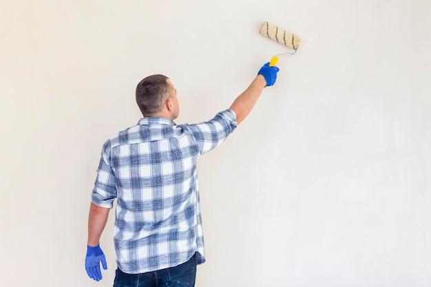 Vue arrière d'un travailleur avec copie espace rouleau de peinture