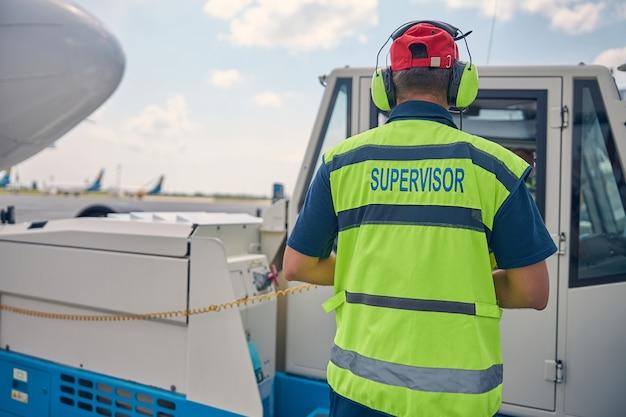 Vue arrière d'un travailleur masculin dans un gilet de sécurité regardant dans un compartiment conducteur