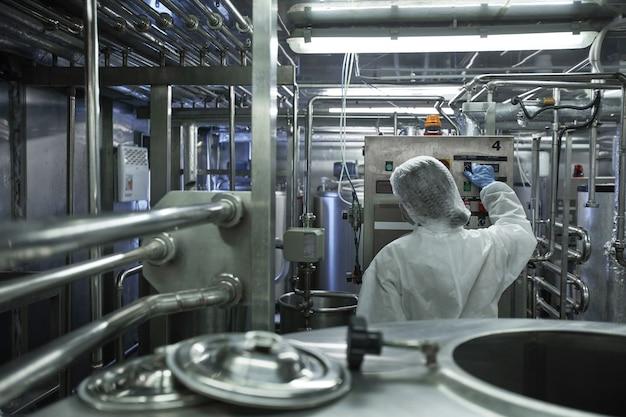 Vue arrière d'une travailleuse méconnaissable faisant fonctionner des unités de machine dans une usine d'aliments propres, espace de copie