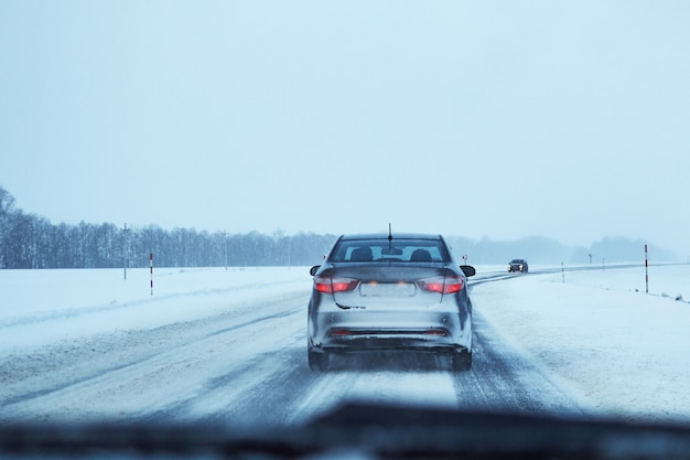 Vue arrière de la voiture sur la route d'hiver enneigée