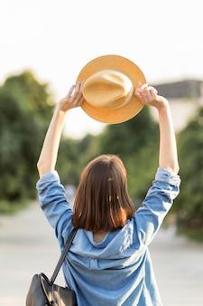 Vue arrière voyageur tenant un chapeau à l'extérieur