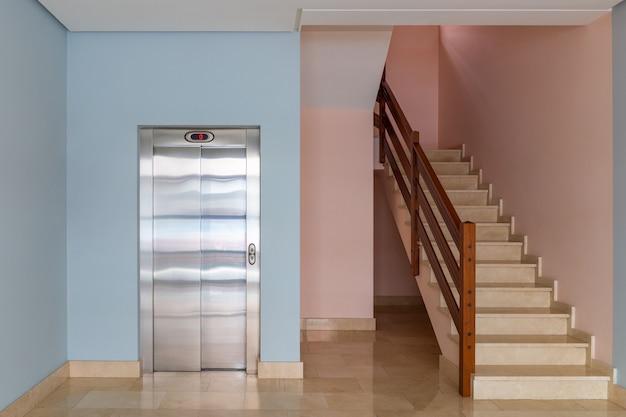 Vue de l'ascenseur et de la cage d'escalier à l'entrée d'un immeuble résidentiel