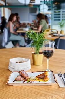Vue d'une assiette de filet de porc avec ananas grillé accompagné d'un verre de vin rouge à une table de restaurant avec des gens en arrière-plan flou.