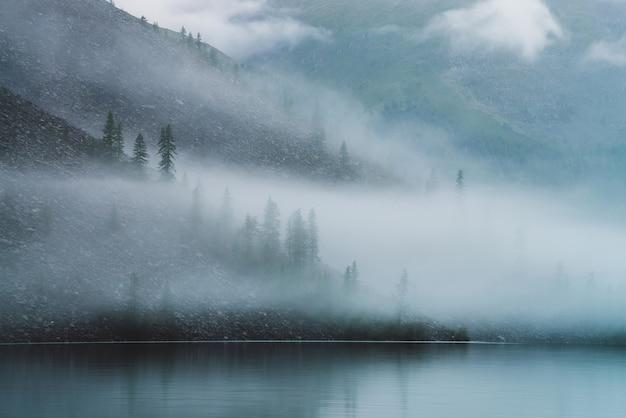 Vue atmosphérique fantomatique sur un lac de montagne tranquille et une pente raide pierreuse avec des conifères dans un brouillard dense.