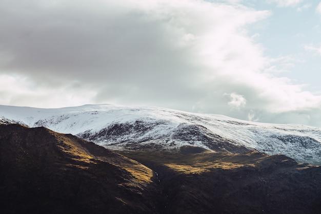 Vue atmosphérique sur les montagnes enneigées au soleil sous un ciel nuageux.