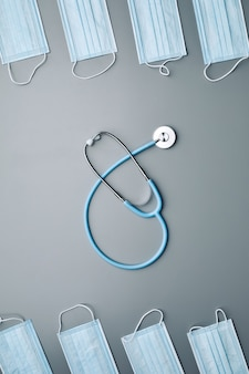 Vue au-dessus de la composition de fond de masques médicaux encadrant le stéthoscope au centre sur fond gris,