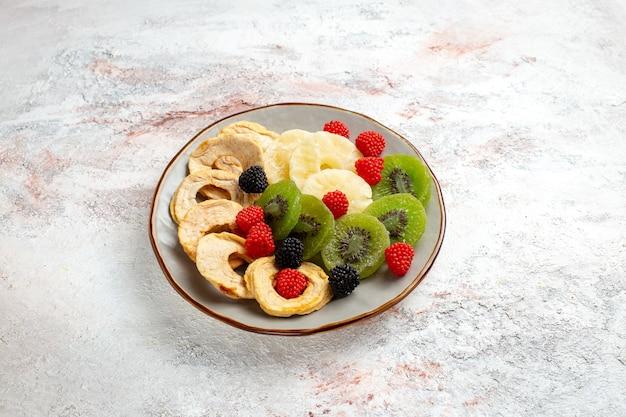 Vue avant des anneaux d'ananas séchés avec des confitures de kiwis séchés et des pommes sur la surface blanche des fruits secs bonbons de sucre sucré