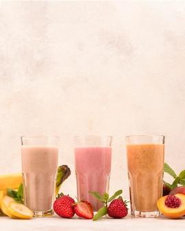 Vue avant de l'assortiment de laits frappés aux fruits dans des verres avec copie espace
