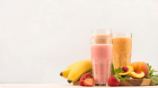 Vue avant de l'assortiment de laits frappés à la fraise et copiez l'espace