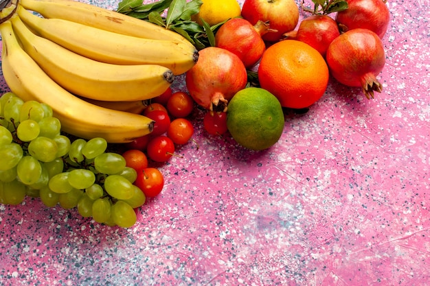 Vue avant de la banane fraîche jaune fruit délicieux avec des raisins et des grenades sur le bureau rose
