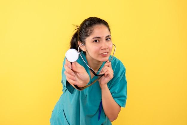 Vue avant béate femme médecin en uniforme montrant un stéthoscope sur fond jaune