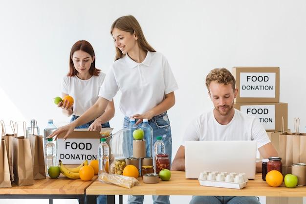 Vue Avant Des Bénévoles Avec Des Boîtes De Dons De Nourriture Et Un Ordinateur Portable Photo gratuit
