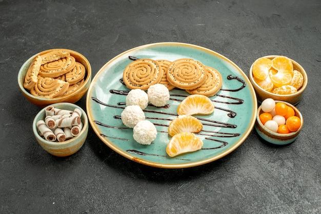 Vue avant des biscuits au sucre avec des bonbons et des mandarines sur la table grise biscuit cookie cake