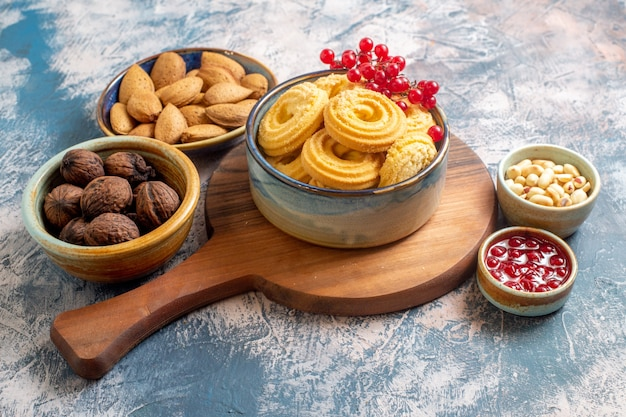 Vue avant des biscuits au sucre avec des noix et de la confiture sur une surface légère
