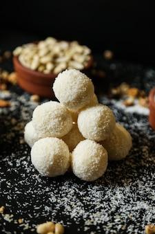 Vue avant des biscuits à la noix de coco avec des flocons de noix de coco et des noix sur fond noir