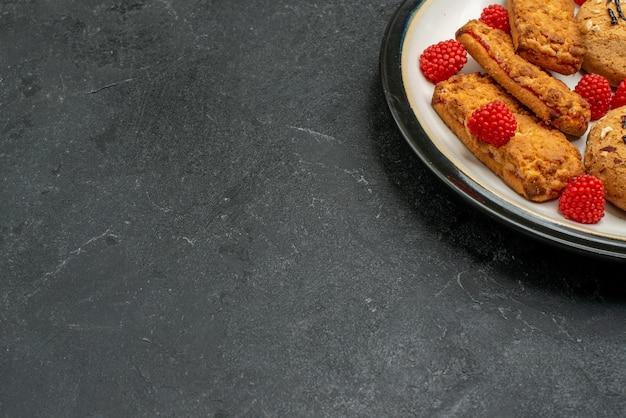 Vue avant des biscuits sucrés délicieux bonbons pour le thé sur l'espace gris