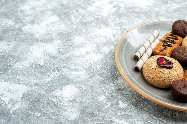 Vue avant des biscuits sucrés à l'intérieur de la plaque sur l'espace blanc