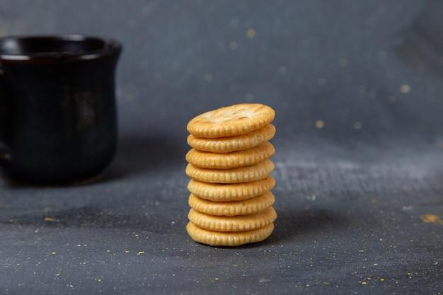 Vue avant des biscuits sucrés ronds avec une tasse de lait noir sur fond gris