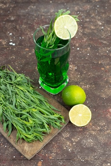 Vue avant de la boisson d'estragon frais à l'intérieur d'un long verre avec des feuilles d'estragon frais sur brun, jus de boisson verte d'estragon