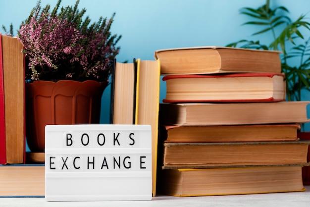 Vue avant de la boîte à lumière avec des livres et des plantes empilés