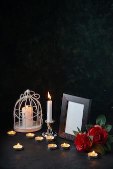 Vue avant des bougies allumées avec cadre photo comme mémoire pour une surface sombre tombée