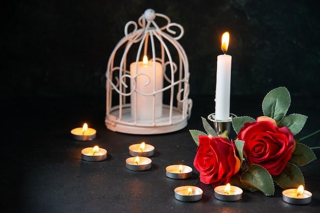 Vue avant des bougies allumées comme mémoire pour une surface sombre tombée