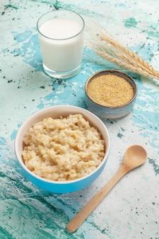 Vue avant de la bouillie et du lait sur la surface bleue de la nourriture de repas de lait de petit déjeuner