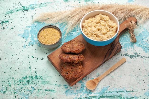 Vue avant de la bouillie avec des escalopes sur le lait de repas de viande de surface bleue