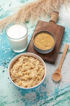 Vue avant de la bouillie savoureuse avec du lait sur la surface bleue du lait de nourriture de petit-déjeuner