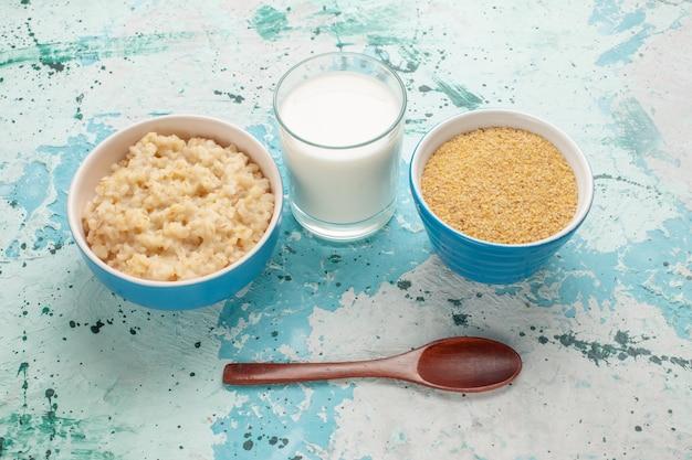 Vue avant de la bouillie savoureuse à l'intérieur de la plaque avec du lait sur la surface bleue petit déjeuner repas de lait matin