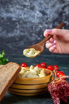 Vue avant des boulettes de viande avec du pain aux tomates cerises fraîches et des légumes verts sur une surface sombre