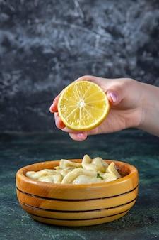 Vue avant des boulettes de viande avec femme pressant le citron en elle sur une surface sombre