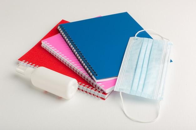 Vue avant des cahiers colorés avec spray et masque sur surface blanche